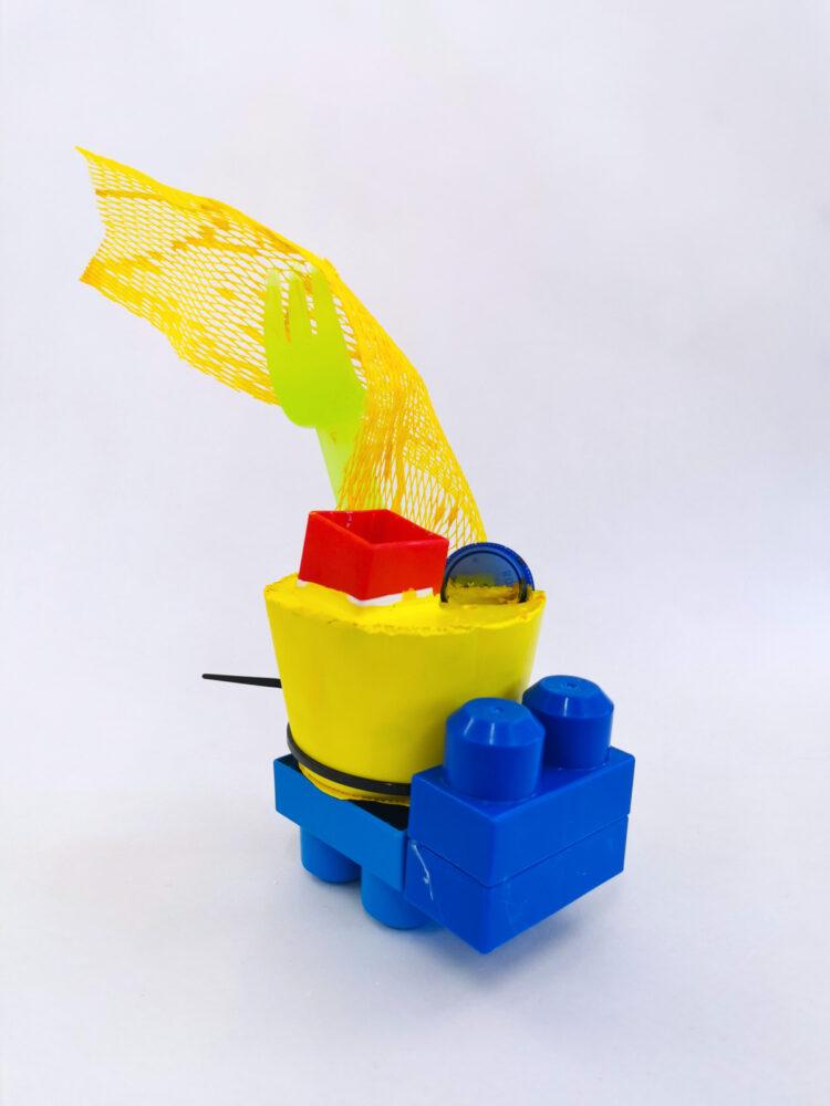 Dino by Celestine Thomas, Mega Bloks, Bottle Lid, Plaster of Paris, Plastic Mesh, Plastic Fork, Cable Tie, and Acrylic Paint.