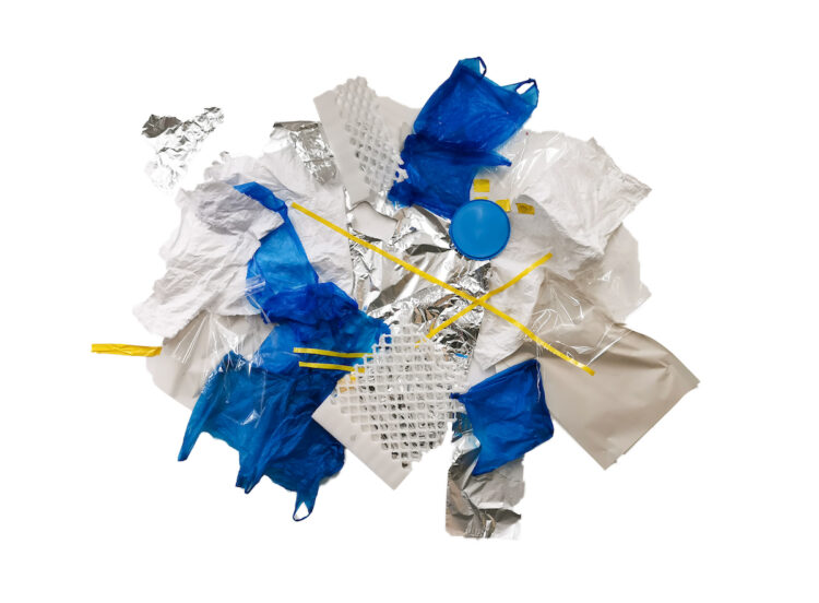 Glacier by Celestine Thomas, Tin foil, plastic bag, tape, paper, cellophane, styrofoam and plastic sweet lid on studio wall.