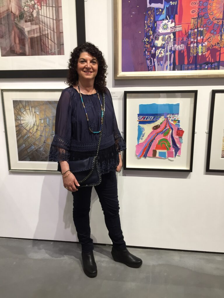 Raina Goran standing next to her painting 'Tel Aviv' at the RI exhibition at the Mall Galleries at the start of April